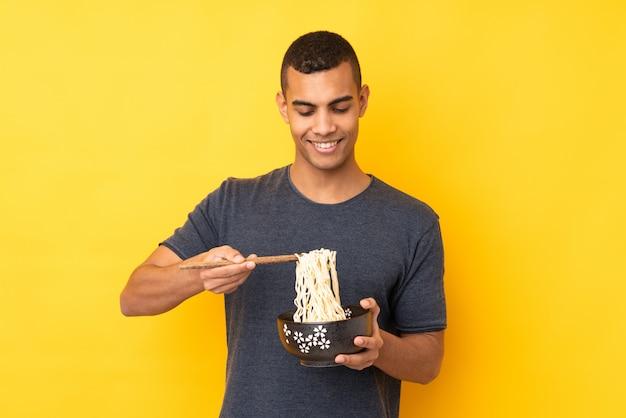 Jonge afrikaanse amerikaanse mens over geïsoleerde gele muur die een kom van noedels met eetstokjes houdt