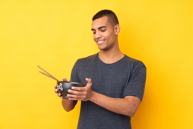 Jonge afrikaanse amerikaanse mens over geïsoleerde gele muur met gelukkige uitdrukking terwijl het houden van een kom van noedels met eetstokjes