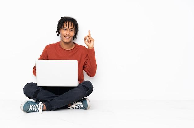 Jonge afrikaanse amerikaanse mensenzitting op de vloer en het werken met zijn laptop die en een vinger in teken van het beste tonen opheffen