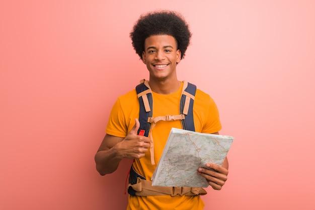 Jonge afrikaanse amerikaanse ontdekkingsreizigermens die een kaart houden die en duim glimlachen opheffen