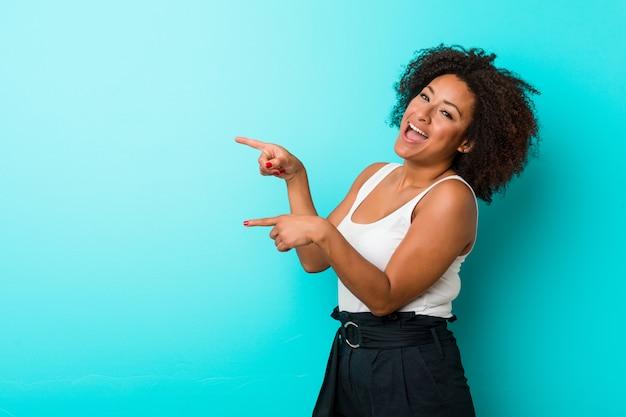 Jonge afrikaanse amerikaanse opgewekte vrouw het richten met weg wijsvingers.