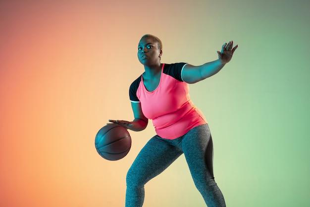 Jonge afrikaanse amerikaanse plus grootte vrouwelijke modellen die op gradiëntmuur trainen