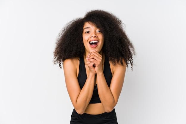 Jonge afrikaanse amerikaanse sportieve vrouw die voor geluk bidden, verbaasde en mond openen die aan voorzijde kijken.