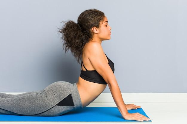 Jonge afrikaanse amerikaanse sportieve vrouw het praktizeren yoga die gebruikend een mat liggen