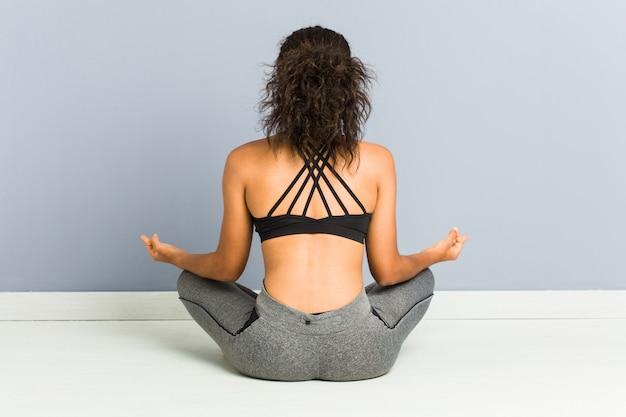 Jonge afrikaanse amerikaanse sportieve vrouwenzitting het praktizeren yoga