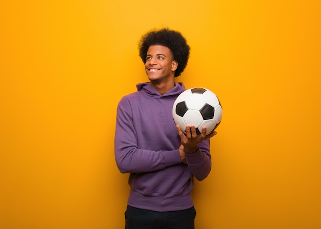 Jonge afrikaanse amerikaanse sportmens die een voetbalbal zeker glimlachen houdt en wapens kruist, die omhoog eruit zien
