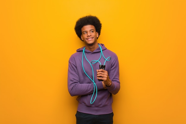 Jonge afrikaanse amerikaanse sportmens die springtouw zeker glimlachen houden en wapens kruisen, die omhoog eruit zien