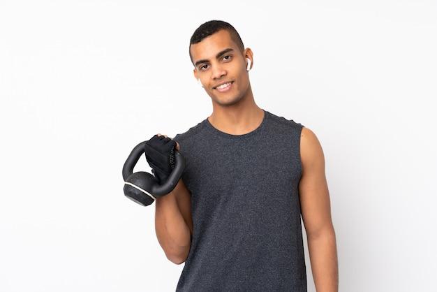 Jonge afrikaanse amerikaanse sportmens over geïsoleerde witte muur die gewichtheffen met kettlebell maken