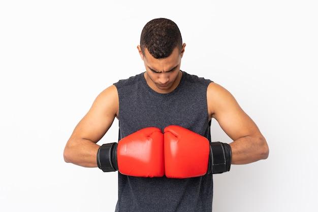 Jonge afrikaanse amerikaanse sportmens over geïsoleerde witte muur met bokshandschoenen