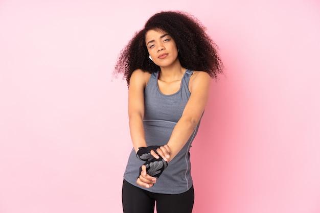 Jonge afrikaanse amerikaanse sportvrouw die op roze het uitrekken zich wapen wordt geïsoleerd
