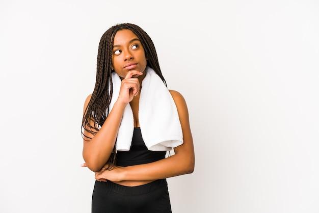 Jonge afrikaanse amerikaanse sportvrouw die opzij kijkt met twijfelachtige en sceptische uitdrukking.