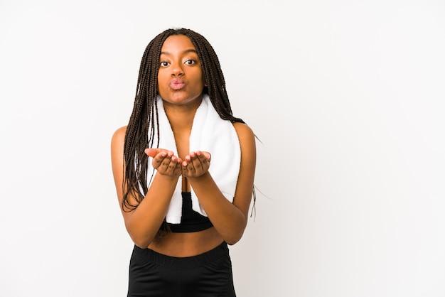 Jonge afrikaanse amerikaanse sportvrouw geïsoleerd die lippen vouwt en palmen houdt om luchtkus te verzenden.