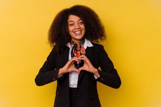 Jonge afrikaanse amerikaanse stewardess die op geel wordt geïsoleerd dat en een hartvorm met handen glimlacht toont.