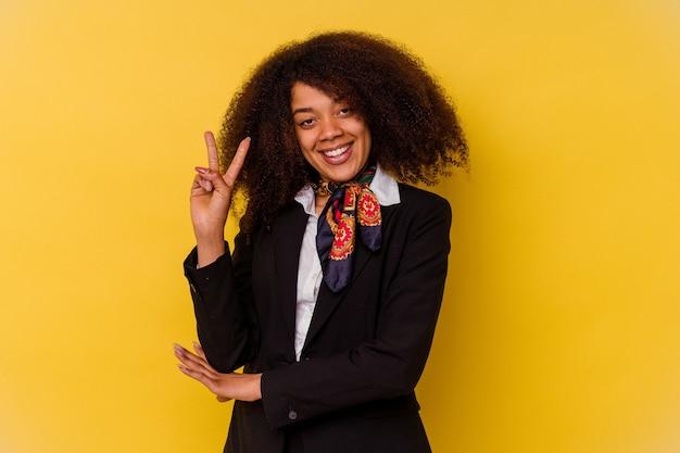 Jonge afrikaanse amerikaanse stewardess die op geel wordt geïsoleerd die nummer twee met vingers toont.