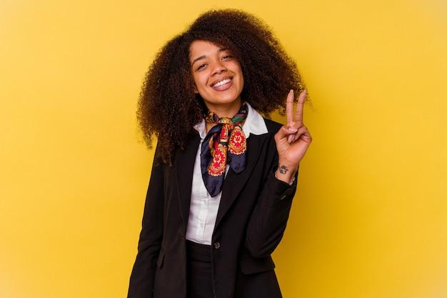 Jonge afrikaanse amerikaanse stewardess die op gele achtergrond wordt geïsoleerd die overwinningsteken toont en breed glimlacht.