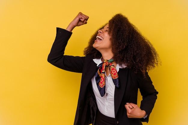 Jonge afrikaanse amerikaanse stewardess die op gele muur wordt geïsoleerd die vuist opheft na een overwinning, winnaarconcept.