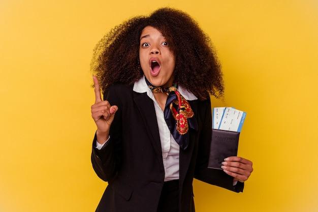 Jonge afrikaanse amerikaanse stewardess die vliegtuigkaartjes houdt die op geel worden geïsoleerd met een idee, inspiratieconcept.