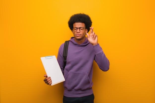 Jonge afrikaanse amerikaanse studentenmens die een klembord houden die vingers kruisen want het hebben van geluk