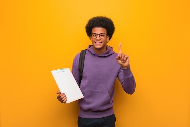 Jonge afrikaanse amerikaanse studentenmens die een klembord houdt dat nummer één toont