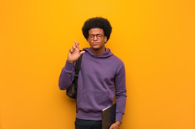 Jonge afrikaanse amerikaanse studentenmens die vingers kruisen voor het hebben van geluk