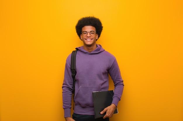 Jonge afrikaanse amerikaanse studentenmens vrolijk met een grote glimlach