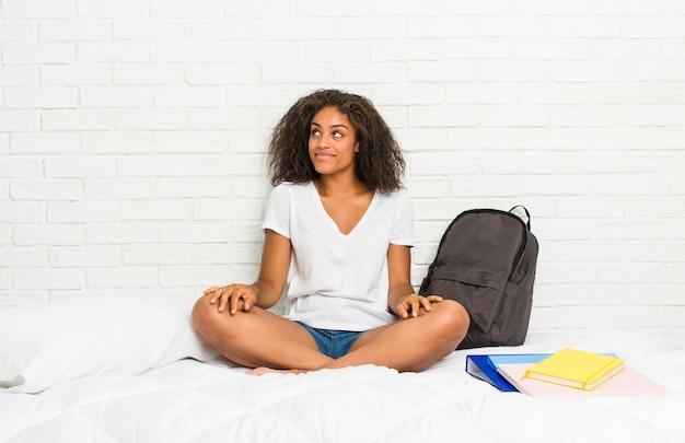 Jonge afrikaanse amerikaanse studentenvrouw die op het bed droomt om doelstellingen te bereiken