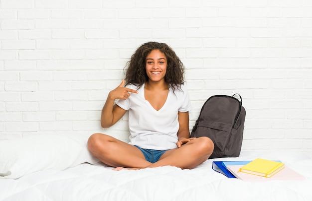 Jonge afrikaanse amerikaanse studentenvrouw op de bedpersoon die met de hand aan een overhemdsexemplaar richten, trots en zeker