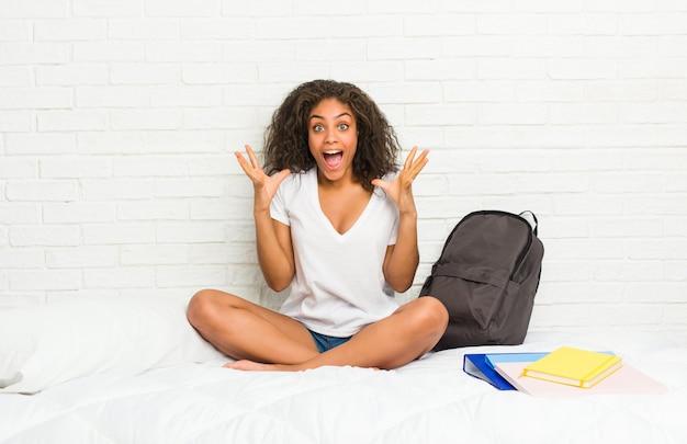 Jonge afrikaanse amerikaanse studentenvrouw op het bed dat een overwinning of een succes viert, is hij verrast en geschokt.