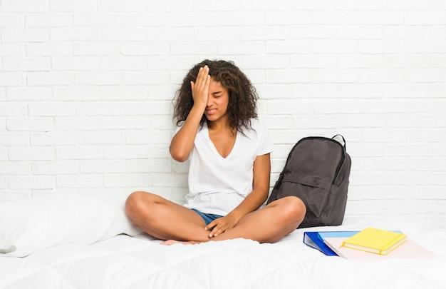 Jonge afrikaanse amerikaanse studentenvrouw op het bed dat iets vergeet, voorhoofd met palm meppend en ogen sluit.