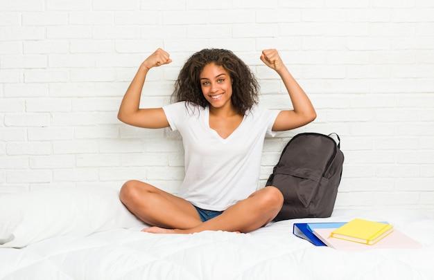 Jonge afrikaanse amerikaanse studentenvrouw op het bed die sterktegebaar met wapens tonen, symbool van vrouwelijke macht
