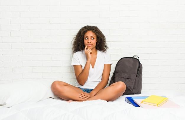 Jonge afrikaanse amerikaanse studentenvrouw op het bed die zijdelings met twijfelachtige en sceptische uitdrukking kijken.