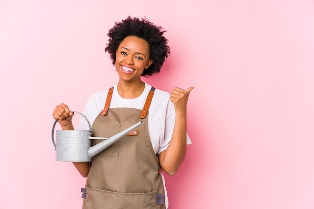 Jonge afrikaanse amerikaanse tuinmanvrouw wijst met duimvinger weg, lachend en zorgeloos.