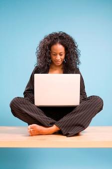 Jonge afrikaanse amerikaanse vrouw die aan laptop werkt