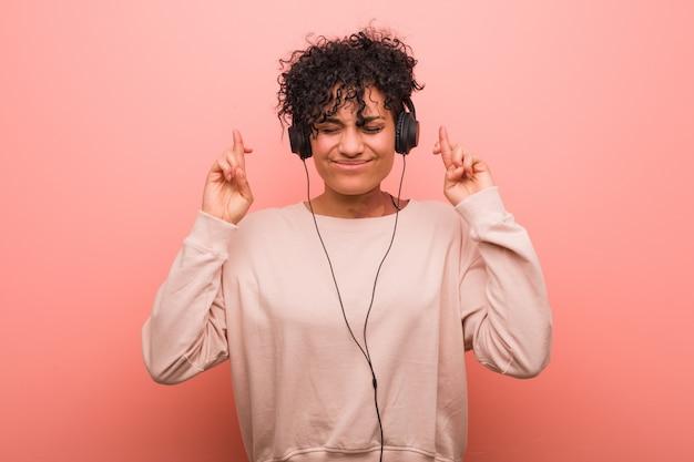 Jonge afrikaanse amerikaanse vrouw die aan muziek luistert die vingers kruist voor het hebben van geluk