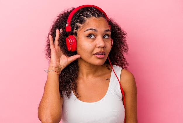 Jonge afrikaanse amerikaanse vrouw die aan muziek met hoofdtelefoons luistert die een roddel proberen te luisteren.