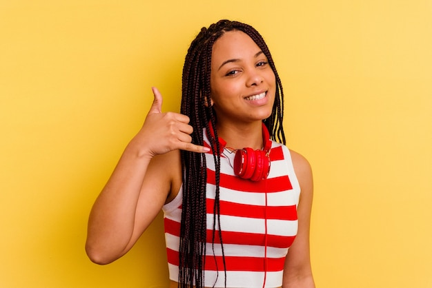 Jonge afrikaanse amerikaanse vrouw die aan muziek met hoofdtelefoons luistert die op gele muur wordt geïsoleerd die een gsm-gebaar met vingers toont