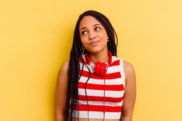 Jonge afrikaanse amerikaanse vrouw die aan muziek met hoofdtelefoons luistert die op gele muur wordt geïsoleerd en droomt van het bereiken van doelstellingen en doeleinden