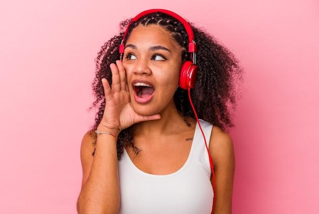 Jonge afrikaanse amerikaanse vrouw die aan muziek met hoofdtelefoons luistert die op roze achtergrond wordt geïsoleerd die schreeuwen en palm dichtbij geopende mond houdt.