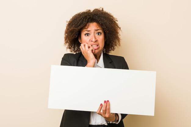 Jonge afrikaanse amerikaanse vrouw die een aanplakbiljet bijtende vingernagels houdt, zenuwachtig en zeer bezorgd.