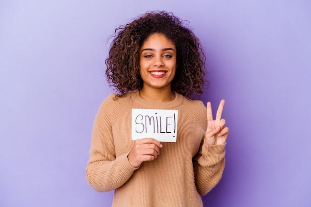 Jonge afrikaanse amerikaanse vrouw die een aanplakbiljet glimlach houdt dat op purpere achtergrond wordt geïsoleerd die nummer twee met vingers toont.