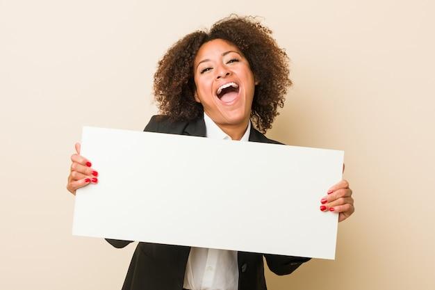 Jonge afrikaanse amerikaanse vrouw die een aanplakbiljet houdt dat een overwinning of een succes viert
