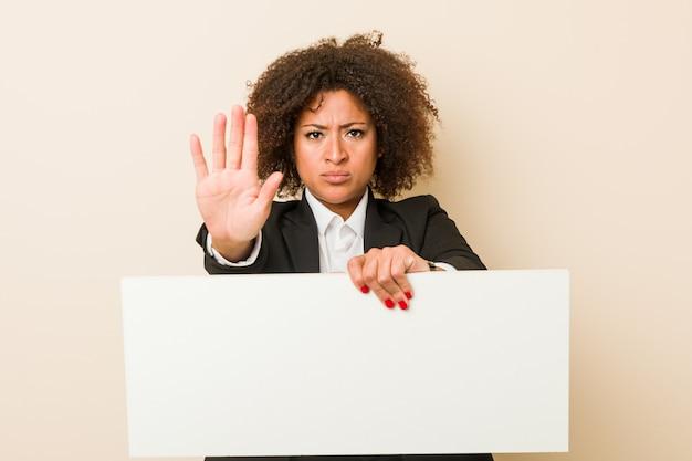 Jonge afrikaanse amerikaanse vrouw die een aanplakbiljet houdt die zich met uitgestrekte hand bevindt die eindeteken toont, dat u verhindert.