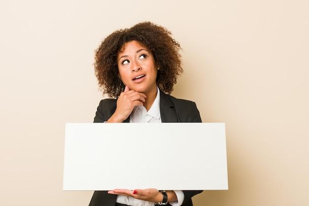 Jonge afrikaanse amerikaanse vrouw die een aanplakbiljet houdt zijdelings kijkend met twijfelachtige en sceptische uitdrukking.