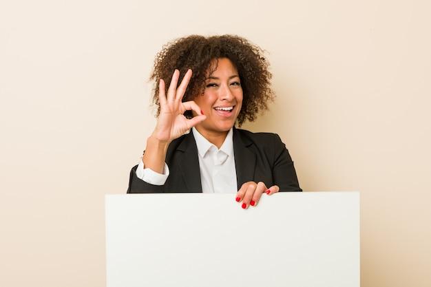 Jonge afrikaanse amerikaanse vrouw die een aanplakbiljet vrolijk en zeker houdt die ok gebaar toont.