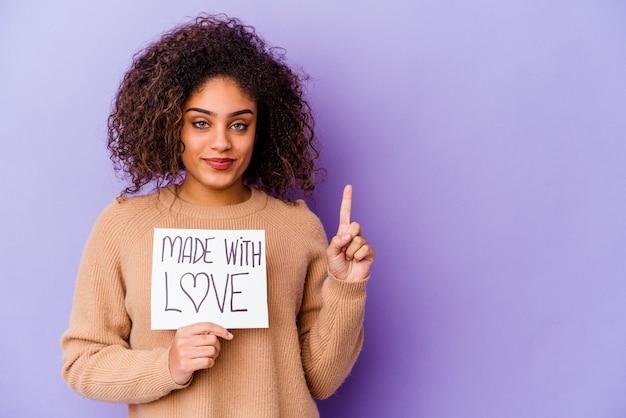 Jonge afrikaanse amerikaanse vrouw die een gemaakt met liefdeaanplakbiljet houdt dat op purpere muur wordt geïsoleerd die nummer één met vinger toont.