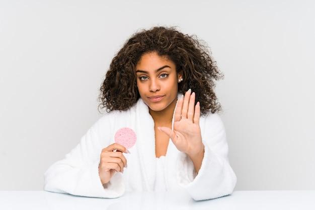 Jonge afrikaanse amerikaanse vrouw die een gezichtsschijf gebruikt die zich met uitgestrekte hand bevindt die stopbord toont, dat u verhindert.