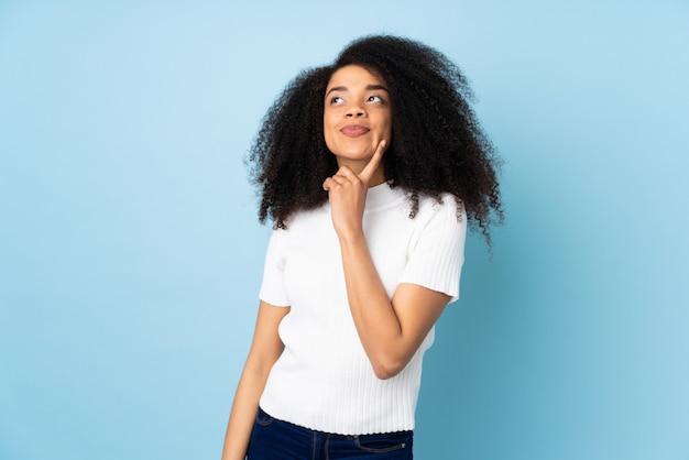 Jonge afrikaanse amerikaanse vrouw die een idee denken terwijl omhoog het kijken