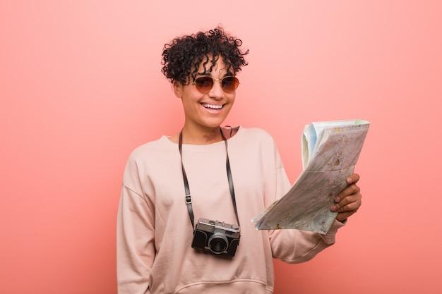 Jonge afrikaanse amerikaanse vrouw die een kaart gelukkig, glimlachend en vrolijk houdt