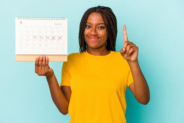 Jonge afrikaanse amerikaanse vrouw die een kalender houdt die op blauwe achtergrond wordt geïsoleerd die nummer één met vinger toont.
