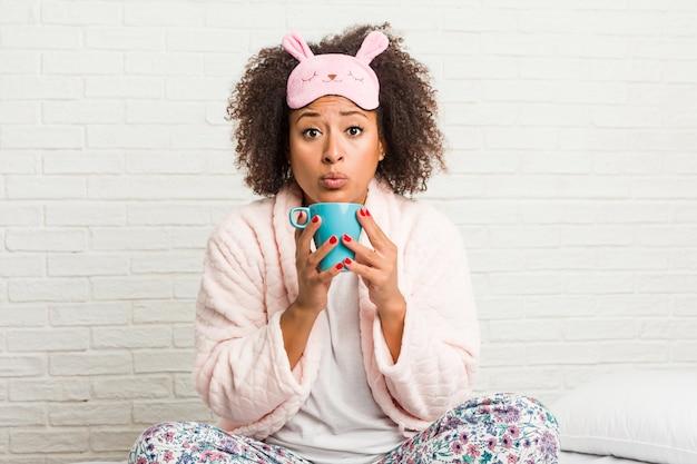 Jonge afrikaanse amerikaanse vrouw die een kop op het bed houdt